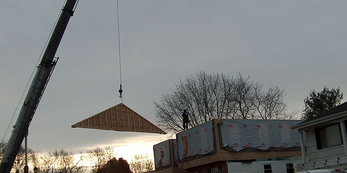 crane bringing a piece of wood over to a worker on top of a house