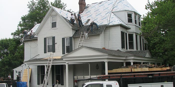 multiple workers on the top of a large house working on roofing