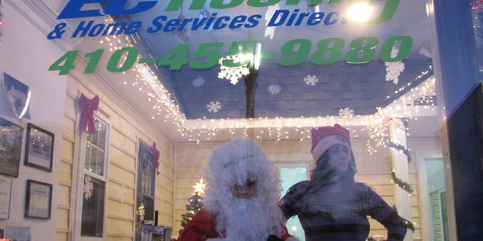 employees dressed as santa and an elf in the ec roofing office window
