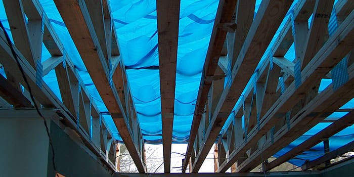 underneath view of roofing beams with tarp over them