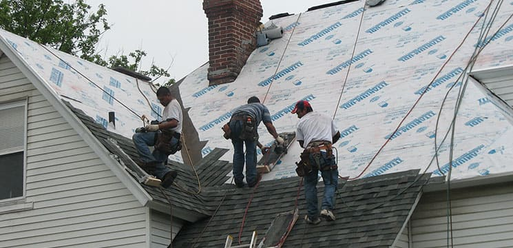 three workers on roof working on shingles for roofing