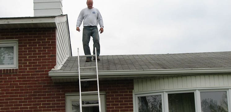 worker walking down a roof towards a ladder to continue the roofing job