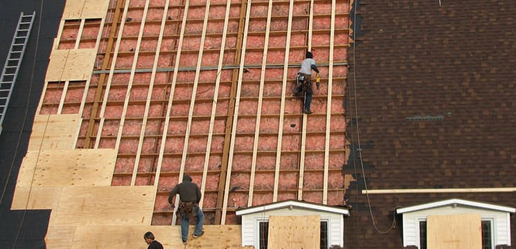 two workers on roof working on insulation and beam work for roofing