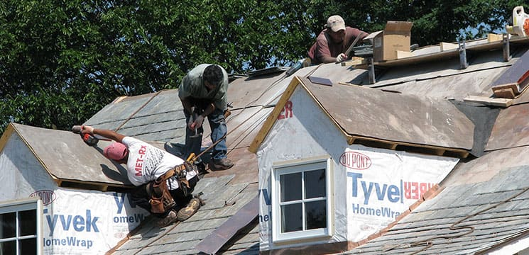 three workers on roof working on shingle roofing
