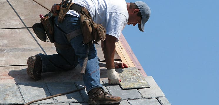 male worker on roof working with shingles