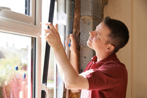 man installing a window replacement in Baltimore md
