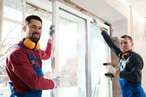 Two men work on window installation and replacement